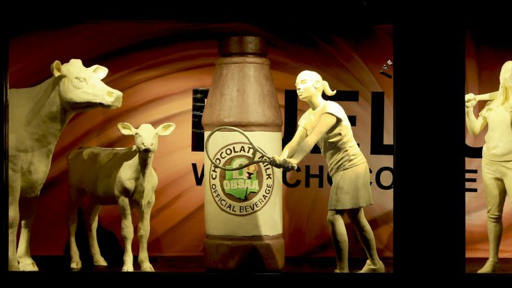 This year, the traditional butter cow and calf are accompanied by four young student-athletes and a larger-than-life bottle of the official beverage that fuels them, chocolate milk.